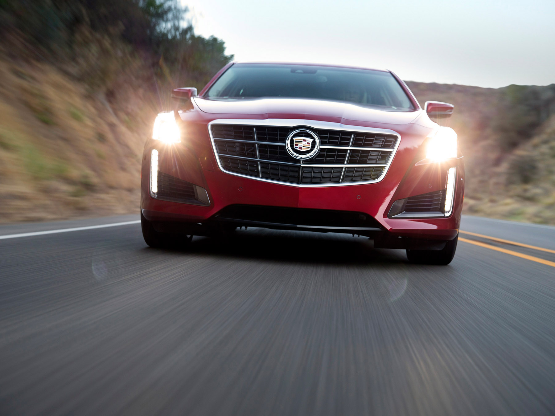 Red Cadillac car driving on the highway
