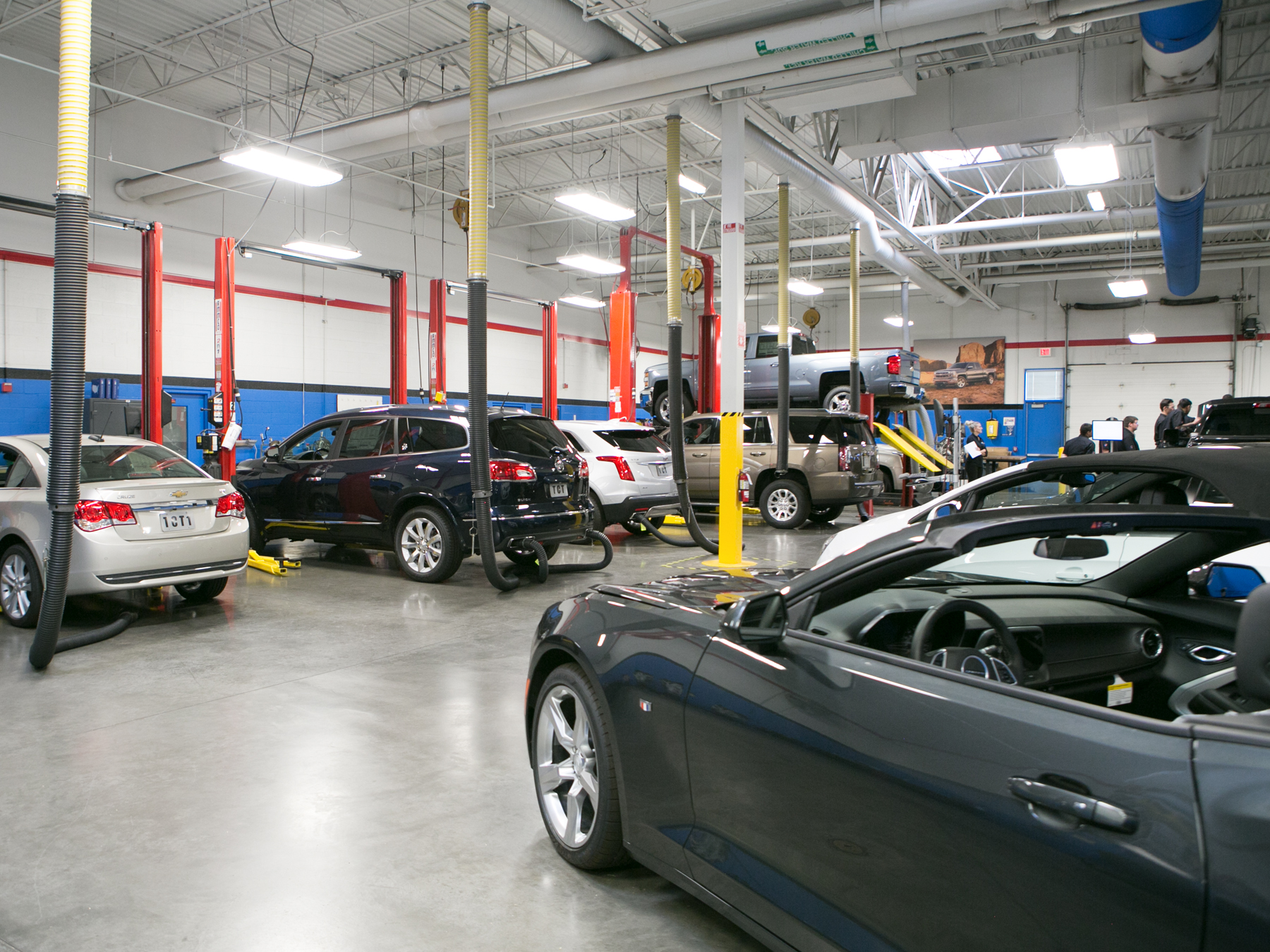 Wide angle photo of cars on lifts in the GM lab