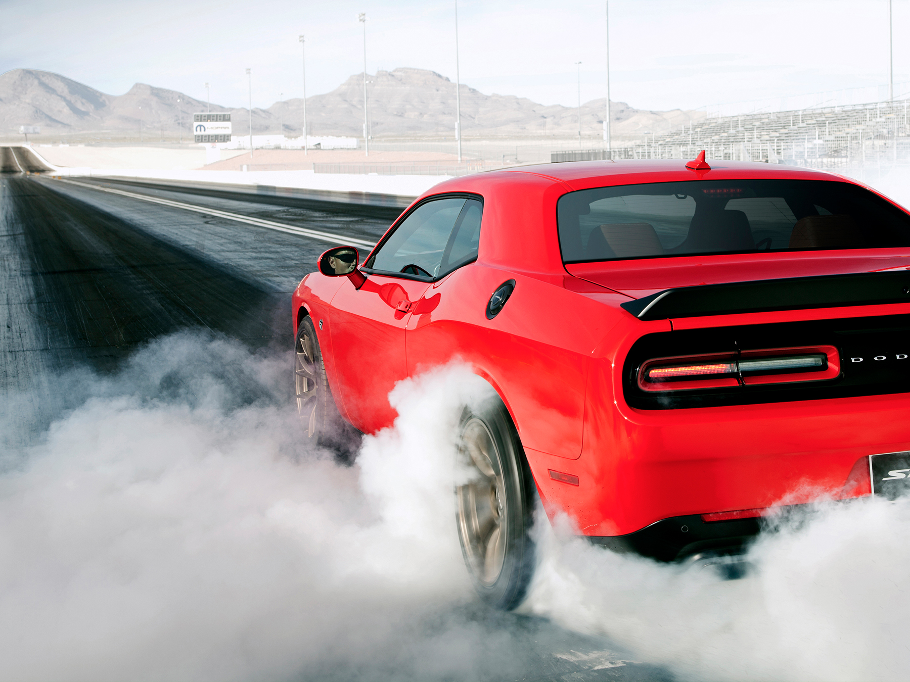 Red dodge Challenger burnout on a drag strip