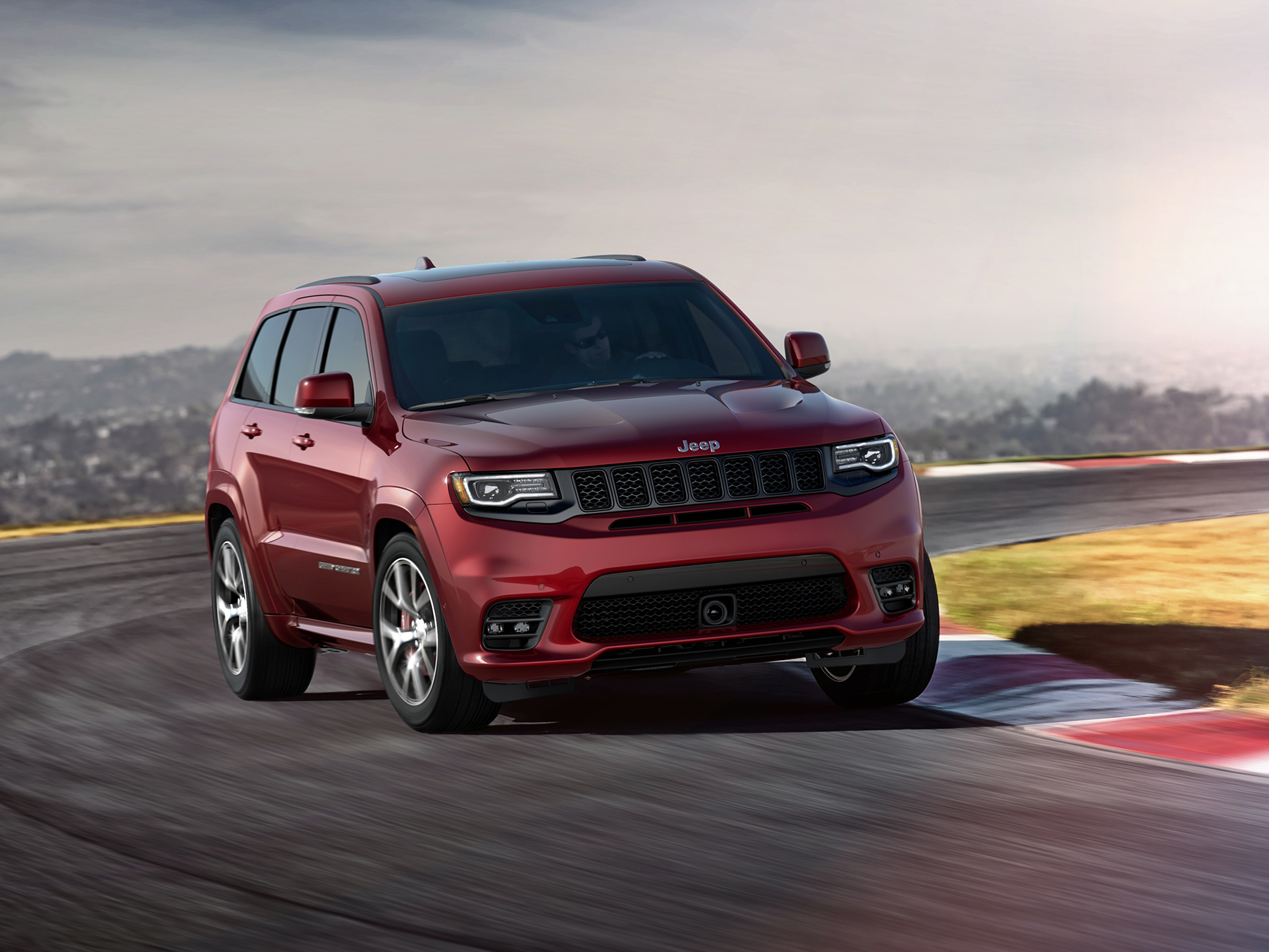 Red Jeep driving on a track