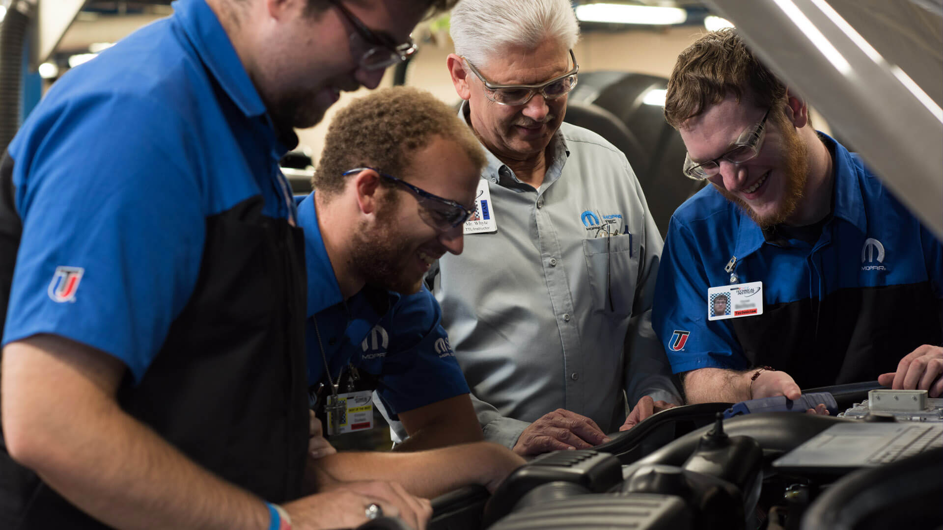UTI students and instructor smiling in the Mopar lab
