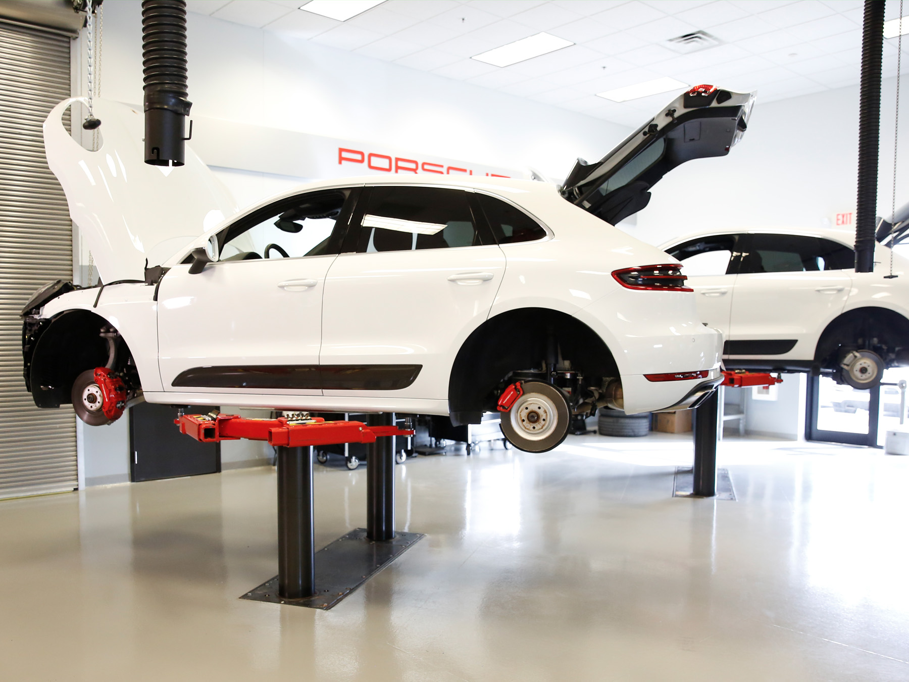 White Porsche car on a lift in the Porsche auto lab