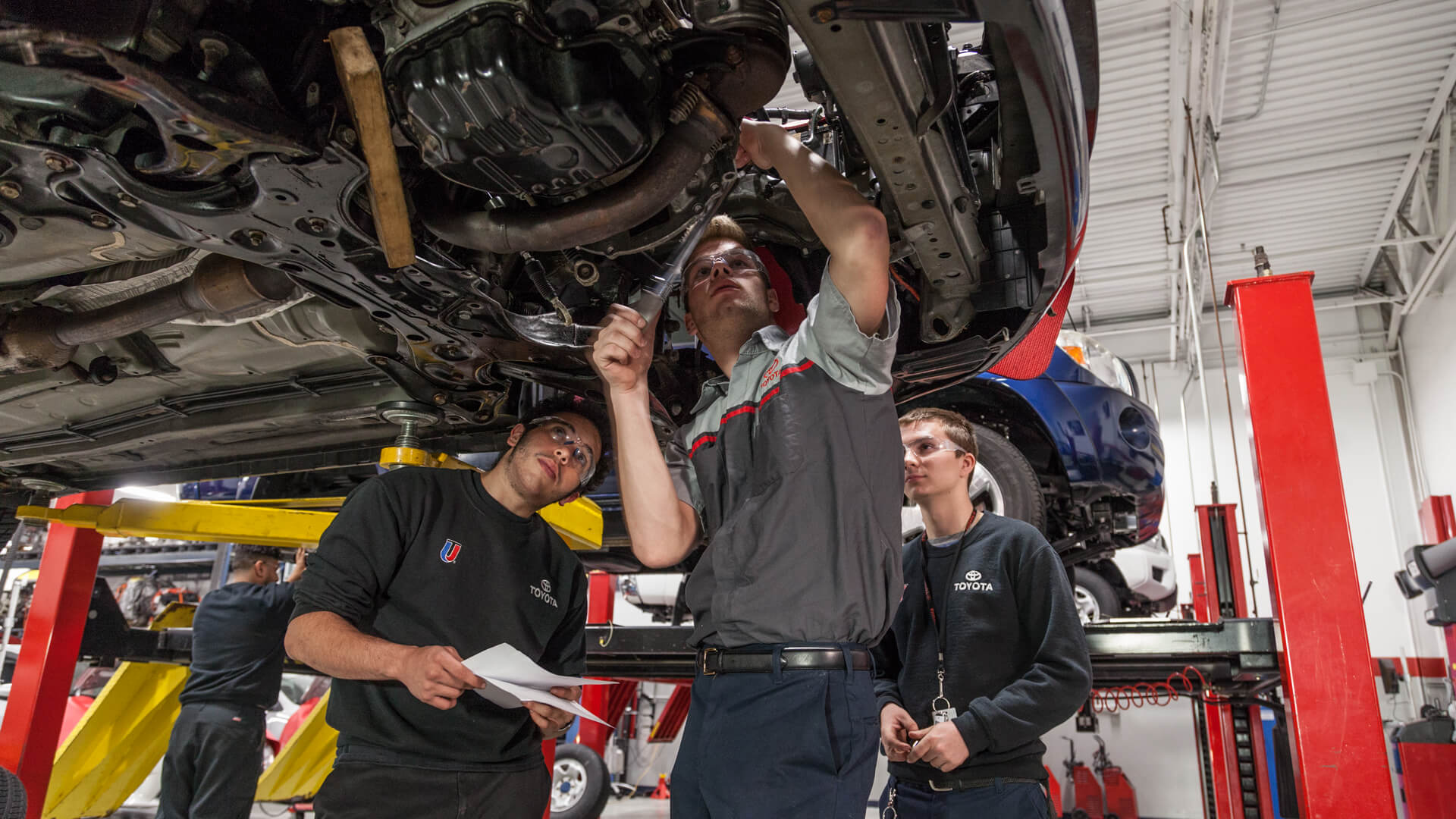 UTI students working underneath the car in the Toyota auto lab