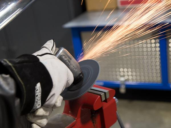 Welding instructor's hands grinding metal creating sparks