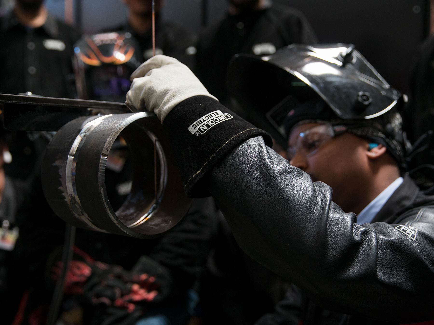 Welding instructor looking at  his weld