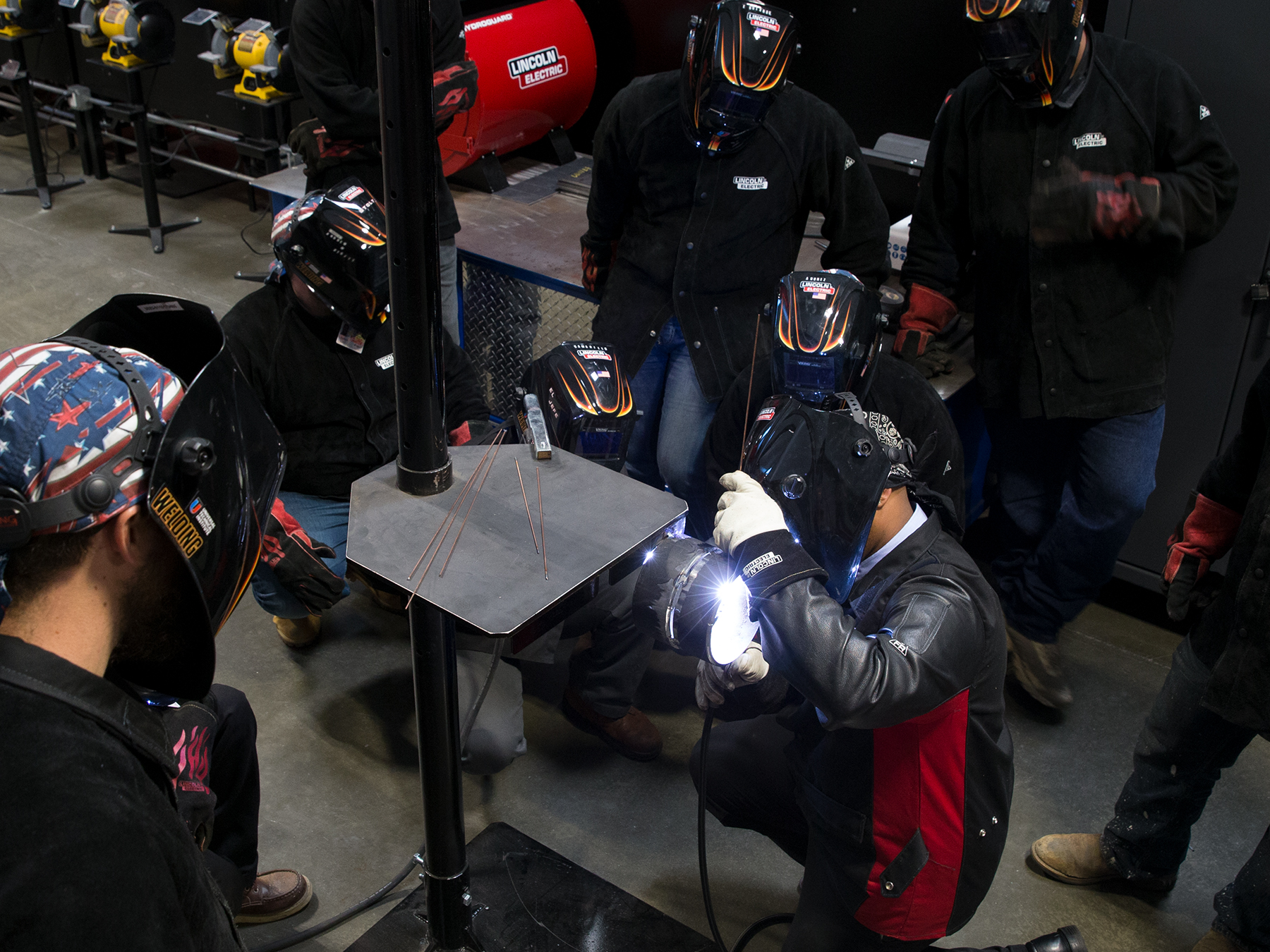 Overhead photo of students watching the instructor welding