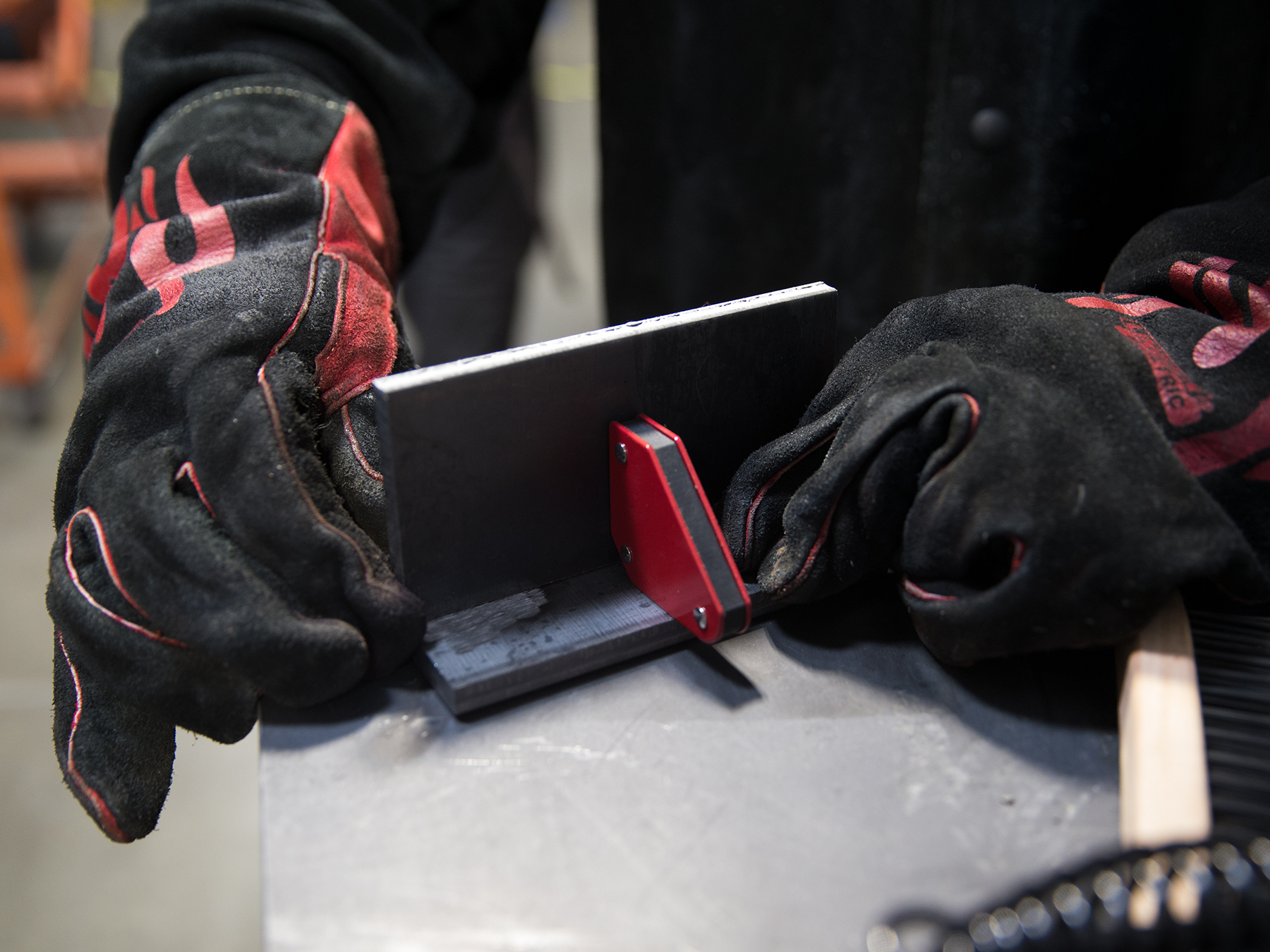 Close up of welding student's hands places to pieces of metal together